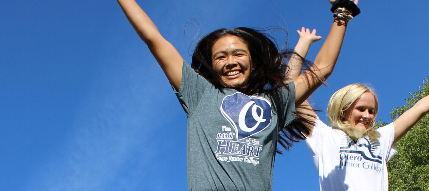Two women wearing OJC t-shirts jump in the air