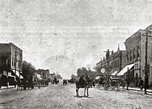 a black-and-white photo showing a horse in the middle of a street