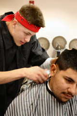 a Cosmetology student cuts a mans hair