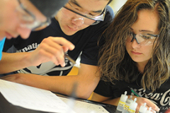 students wearing protective eyeglasses work on a science assignment