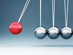 Newton's cradle with a red ball swinging