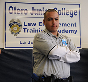 a Law Academy student standing in front of a LETA sign