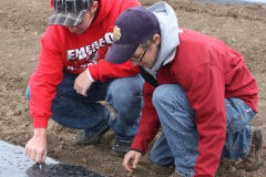 two students wearing red hoodies work with materials on the ground