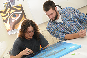 two students work on an art project